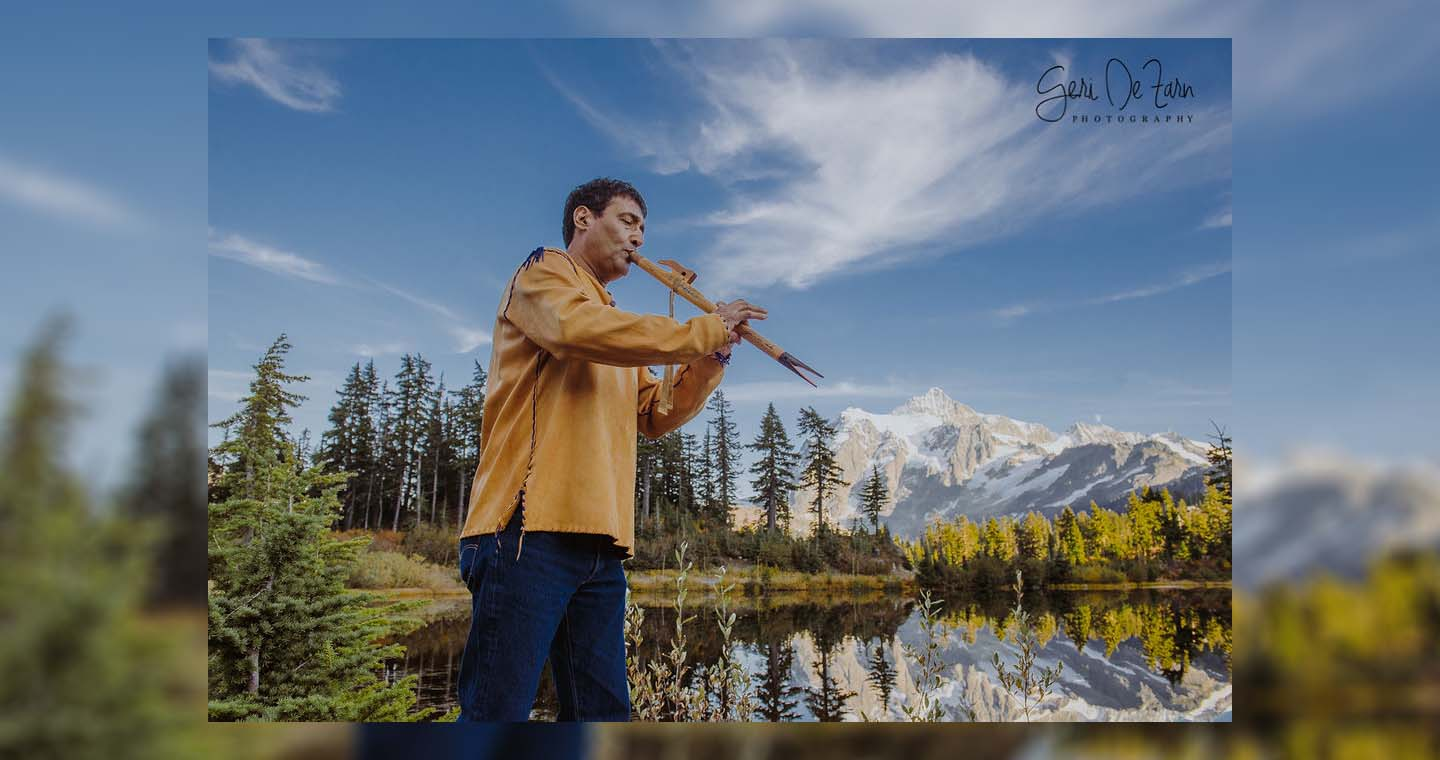 Peter Ali - a man with a tan shirt and blue jeans plays a flute-like instrument. A tranquil pond, trees, and blue sky with fluffy clouds is in the background